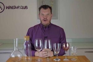 Campbell from WinedUp Club sitting at a table with a selection of good wine glasses and bad wine glasses and glassware